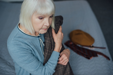 upset senior woman with grey hair sitting on bed and holding jacket at home