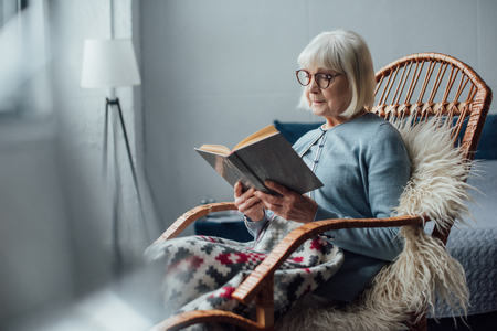 senior woman in glasses sitting in wicker rocking chair and reading book at home Standard-Bild - 116298346