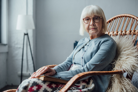 senior woman sitting in wicker rocking chair at home and looking at camera 版權商用圖片