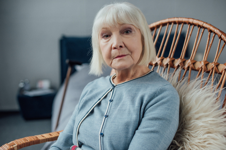 serious senior woman sitting in wicker rocking chair at home and looking at camera