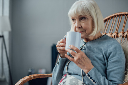 senior woman sitting in wicker rocking chair and drinking coffee at home