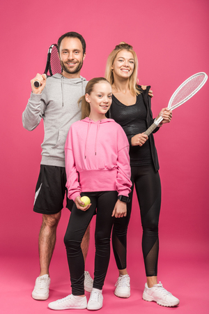athletic family holding tennis rackets and ball, isolated on pink Stockfoto