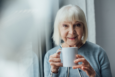 smiling senior woman holding cup of coffee at home and looking at camera