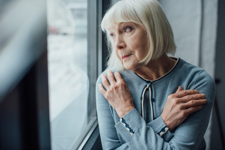 pensive senior woman with hands crossed looking through window at home