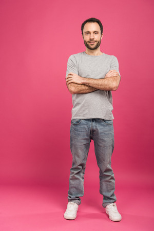 happy handsome man posing with crossed arms, on pink Stock Photo