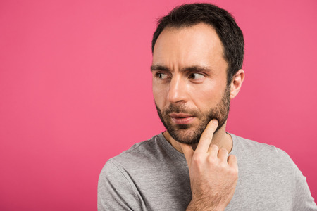 portrait of thoughtful man looking away, isolated on pink