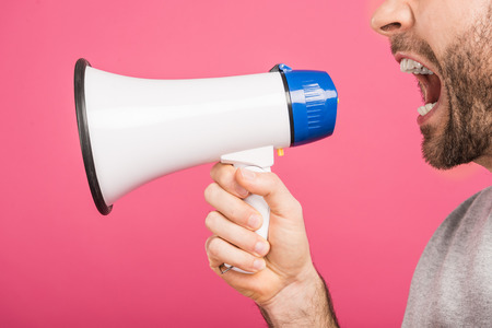 cropped view of angry man screaming with megaphone, isolated on pink Stock Photo