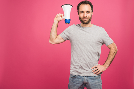 smiling man holding megaphone, isolated on pink