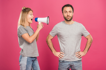 angry girlfriend shouting with megaphone at boyfriend, isolated on pink
