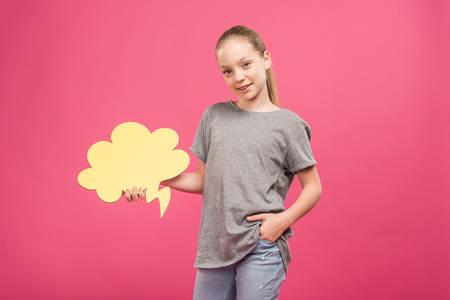 adorable youngster holding yellow thought bubble, isolated on pink