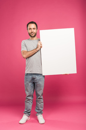 handsome man posing with blank board, isolated on pink