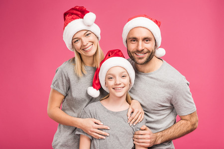 portrait of smiling family with daughter in santa hats, isolated on pink Standard-Bild