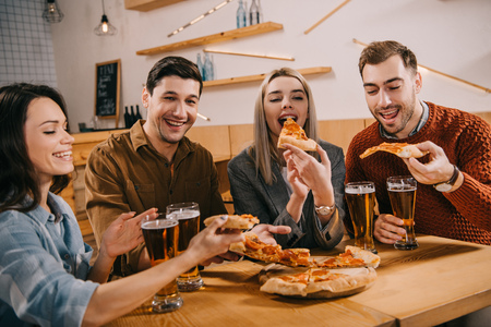happy woman eating pizza near friends in bar
