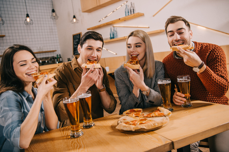 happy friends eating pizza near glasses of beer in bar