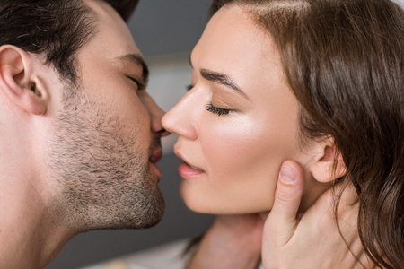 close up of handsome man kissing attractive woman Banco de Imagens