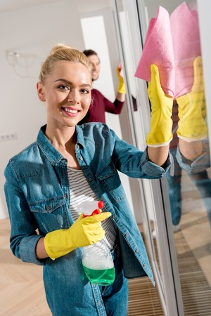 attractive girl cleaning window with rag and spray, smiling and looking at camera in apartment Imagens