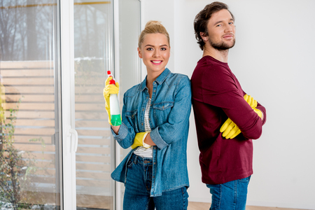 attractive girl and handsome man in rubber gloves smiling and looking at camera