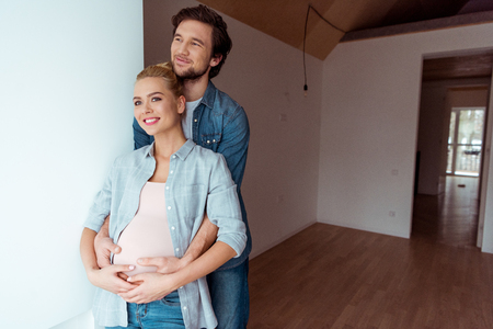 smiling man keeping hands on belly of pregnant wife Banco de Imagens