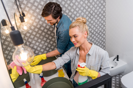 smiling couple in rubber gloves cleaning mirrors in bathroom