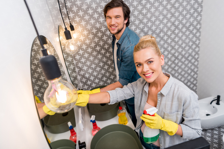 handsome man and attractive girl in rubber gloves girl cleaning mirrors and looking at camera in bathroom