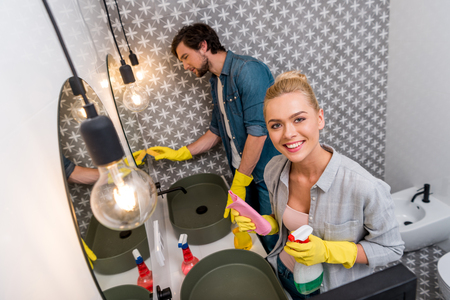 smiling girl in rubber gloves holding spray and rag while husband cleaning mirror in bathroom Stock Photo