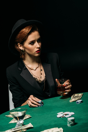 attractive girl in jacket and hat holding glass of whiskey at poker table in casino