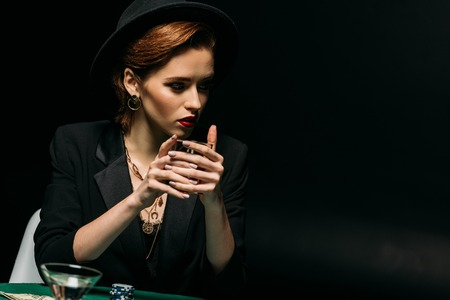 attractive girl in jacket and hat holding glass of whiskey at poker table in casino and looking away 免版税图像