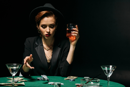 attractive girl in jacket and hat holding glass of whiskey and playing poker in casino Stock Photo