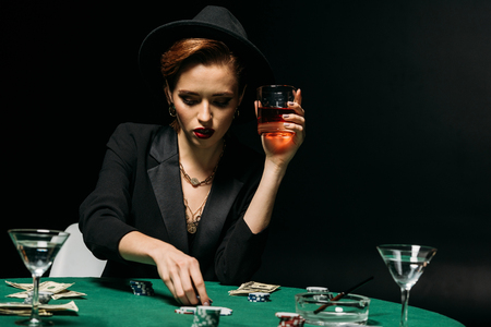 beautiful girl in jacket and hat holding glass of whiskey and playing poker in casino Stock Photo
