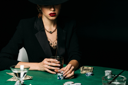 attractive girl in jacket and hat holding glass of whiskey and taking poker chip in casino