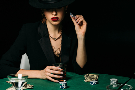 attractive girl in jacket and hat holding glass of whiskey and poker chip at table in casino