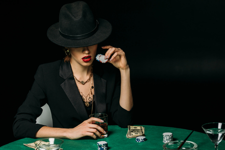 attractive girl in jacket and hat holding glass of whiskey and poker chips at table in casino