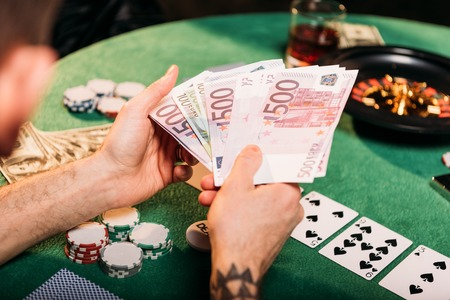 cropped image of tattooed man holding euro banknotes at poker table in casino Stock Photo - 116294226