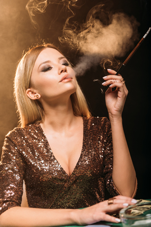 portrait of attractive girl smoking cigarette at poker table in casino 版權商用圖片