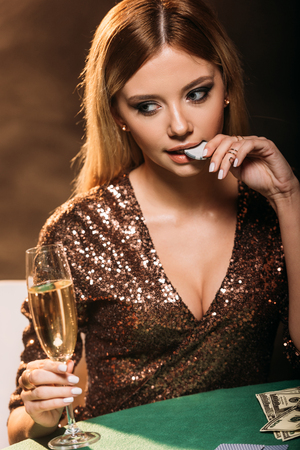 attractive girl holding glass of champagne and biting poker chip at table in casino