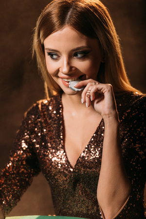 attractive smiling girl in sparkling dress biting poker chip at table in casino and looking away Stock Photo - 116294394