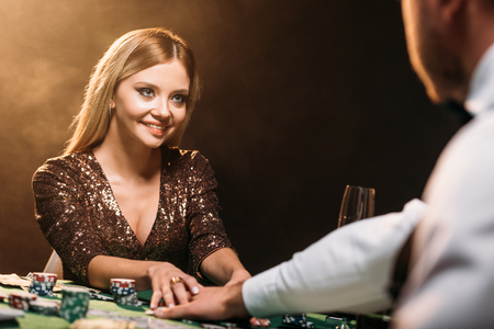 happy attractive girl taking poker chips and looking at croupier at casino