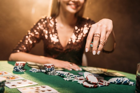 cropped image of smiling girl playing poker at table in casino