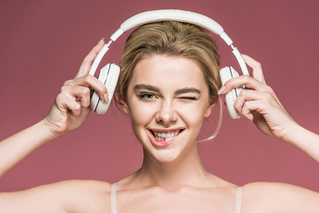beautiful smiling girl winking and listening music with headphones, isolated on pink 版權商用圖片 - 116320548