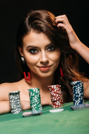 attractive girl leaning on table with poker chips and looking at camera isolated on black Stock Photo - 116320557