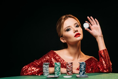 attractive girl in red shiny dress leaning on table, holding poker chip and looking at camera isolated on black