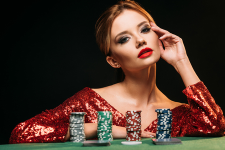 beautiful girl in red shiny dress leaning on table with poker chips and looking at camera isolated on black Stock fotó