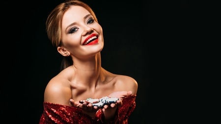 smiling attractive girl in red shiny dress holding casino chips isolated on black Stock Photo