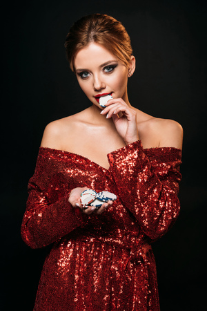 attractive girl in red shiny dress holding and biting poker chips isolated on black