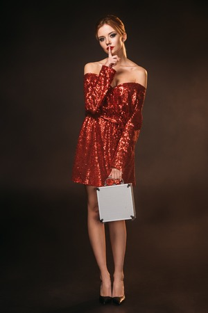 attractive girl in red shiny dress holding money box and showing silence gesture isolated on black