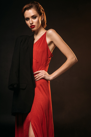 attractive girl in red dress and black jacket on one shoulder looking at camera isolated on black