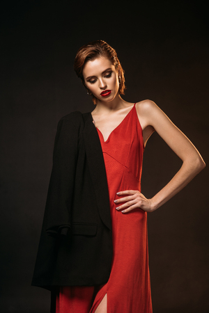 attractive girl in red dress and black jacket on one shoulder looking down isolated on black