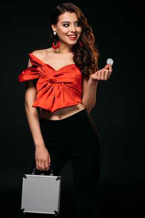 happy beautiful brown haired girl in red corset holding money box and casino chips isolated on black