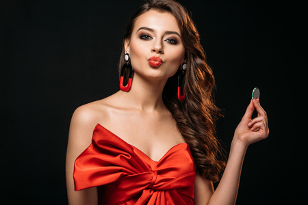 beautiful brown haired girl in red corset holding casino chip and pretending kissing isolated on black Фото со стока - 116320104