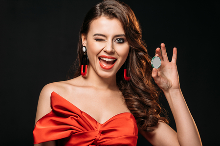 excited brown haired girl in red corset holding casino chip and winking isolated on black Imagens